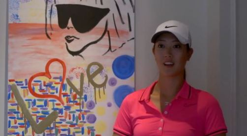 Michelle Wie with one of her paintings
